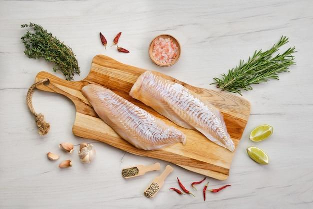 木製のまな板に調味料とハドックの切り身の上面図 Premium写真