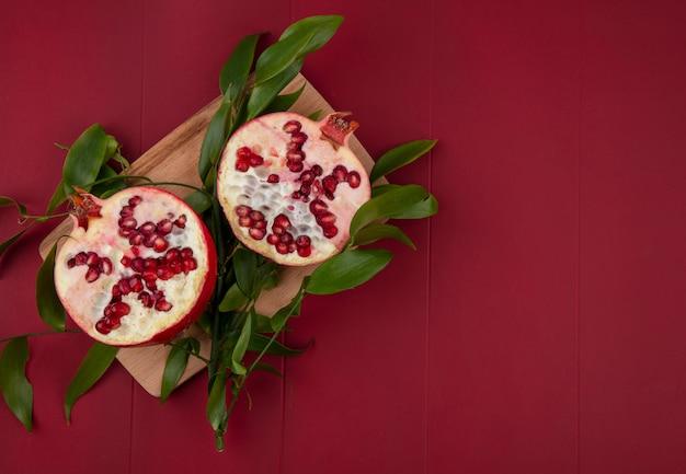 Вид сверху на половину граната и листья на разделочной доске на красной поверхности Бесплатные Фотографии