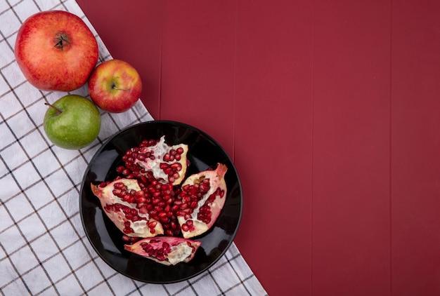 赤い表面に市松模様のタオルの上に着色されたリンゴと黒のプレートにザクロの半分のトップビュー 無料写真