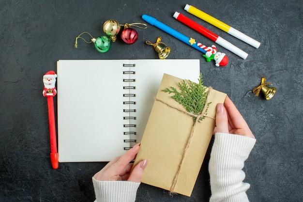 黒の背景に装飾アクセサリーを書く新年あけましておめでとうございますとスパイラルノートにギフトを手に上面図 無料写真