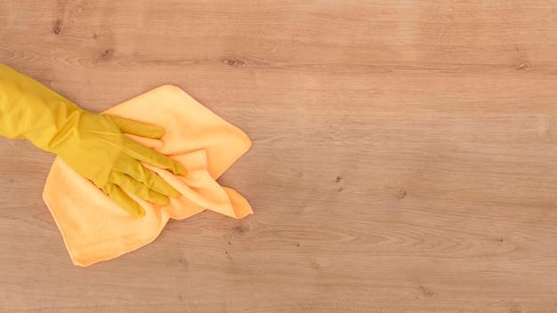 Вид сверху ручной чистки деревянной поверхности тканью Бесплатные Фотографии