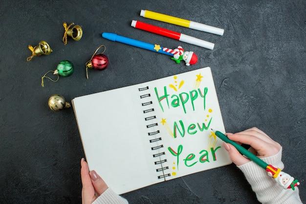黒の背景に装飾アクセサリーを書く新年あけましておめでとうございますとスパイラルノートにペンを持っている手の上面図 無料写真