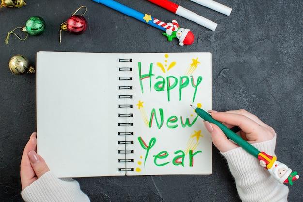 黒いテーブルに装飾アクセサリーを書く新年あけましておめでとうございますとスパイラルノートにペンを持っている手の上面図 無料写真