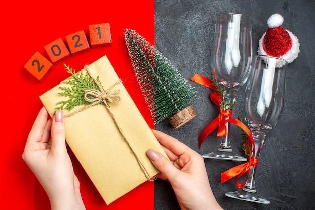 빨간색과 검은 색 배경에 아름 다운 선물 크리스마스 트리 번호 산타 클로스 모자를 들고 손의 상위 뷰 무료 사진