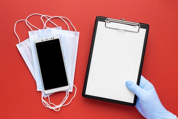 Вид сверху руки, держащей буфер обмена с медицинскими масками и смартфоном Бесплатные Фотографии