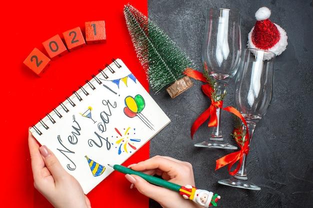 어둡고 빨간색 배경에 새 해 그리기 및 크리스마스 트리 유리 받침 번호와 나선형 노트북을 들고 손의 상위 뷰 무료 사진
