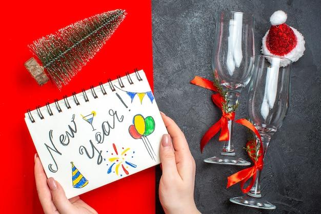 어둡고 빨간색 배경에 새 해 그리기 및 크리스마스 트리 유리 받침과 나선형 노트북을 들고 손의 상위 뷰 무료 사진