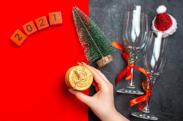 빨간색과 검은 색 배경에 누적 된 쿠키 크리스마스 트리 번호 산타 클로스 모자를 들고 손의 상위 뷰 무료 사진