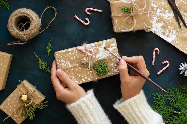 ペンキでクリスマスプレゼントを飾る手の上面図 無料写真