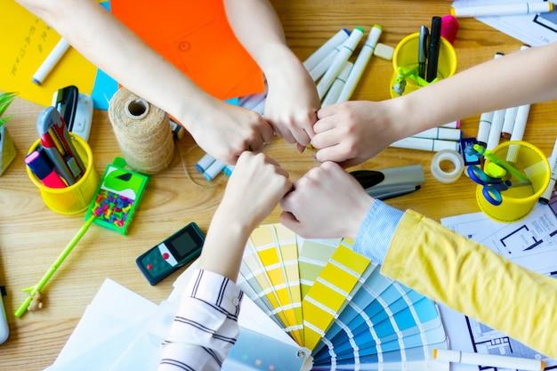クリエイティブ・オフィスの机の上に拳を一緒に入れてビジネス人々の手の平面図です。色見本、部屋のレイアウト、事務用品のテーブルにいる建築家やインテリアデザイナー。チームワークの概念 Premium写真