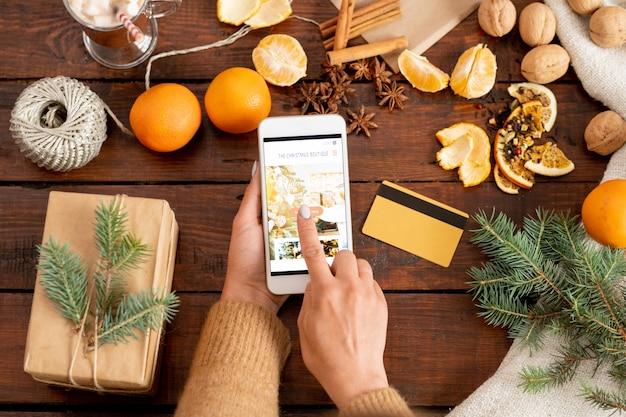 オンラインショップに入る女性のスマートフォンのディスプレイ上のスタートボタンに触れる手の平面図 Premium写真