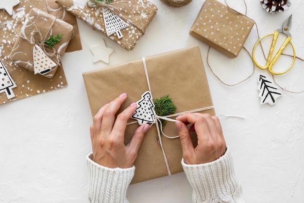 Вид сверху рук, связывающих рождественские подарки Бесплатные Фотографии