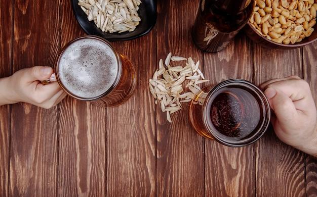 Вид сверху руки с кружками пива и соленые закуски семена подсолнечника на деревенском дереве Бесплатные Фотографии