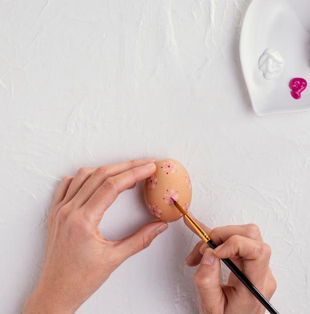 イースターエッグを描く絵筆で手の上面図 無料写真