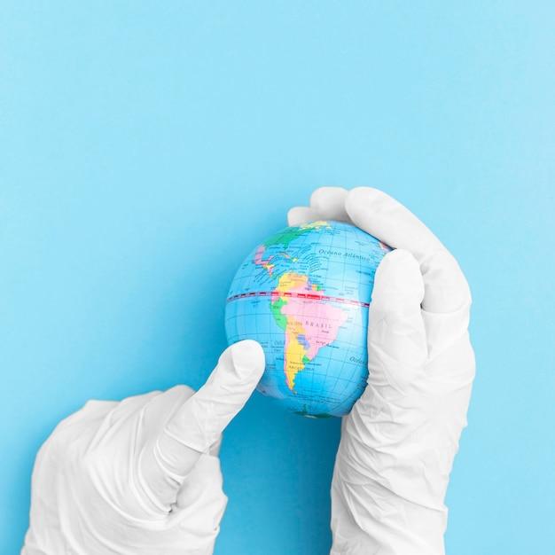 Взгляд сверху рук с хирургическими перчатками держа земной шар Бесплатные Фотографии