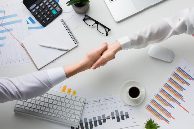 Вид сверху рукопожатия над столом с клавиатурой и диаграммами Premium Фотографии