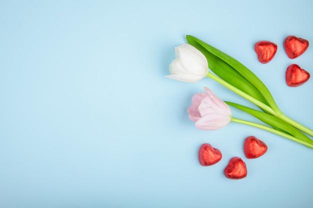 コピースペースを持つ青いテーブルにピンク色のチューリップと赤い箔でハート型のチョコレート菓子のトップビュー 無料写真