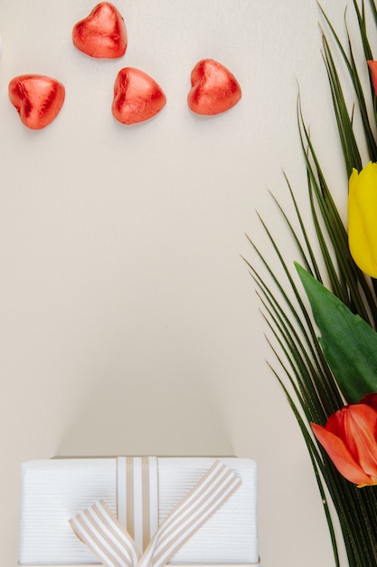 コピースペース付きの白いテーブルに赤い箔、ギフトボックス、色とりどりのチューリップの花束に包まれたハート型のチョコレート菓子の上から見る 無料写真