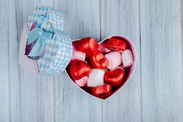 灰色の木製のテーブルにハート型のギフトボックスにピンクのマシュマロと赤い箔に包まれたハート型のチョコレート菓子のトップビュー 無料写真