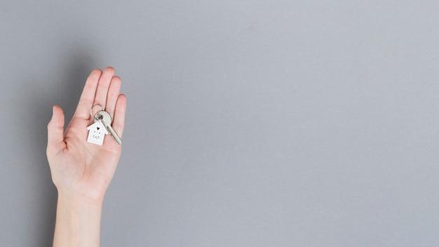 Вид сверху человеческой руки, держащей ключ от дома на сером фоне Premium Фотографии