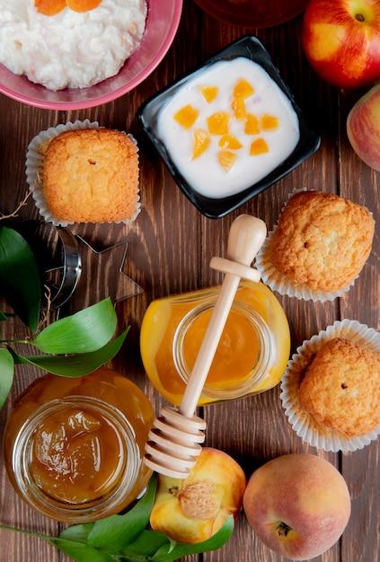 Вид сверху банок варенья как персик и слива с кексы персики творог на деревянной поверхности Бесплатные Фотографии