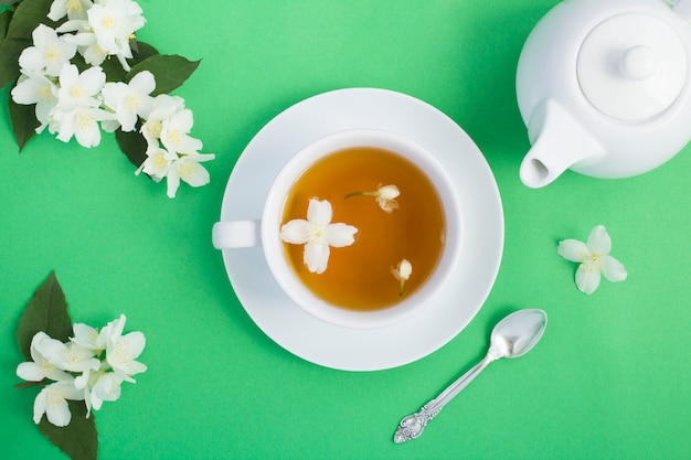Вид сверху жасминового чая в белой чашке, чайнике и цветах Premium Фотографии
