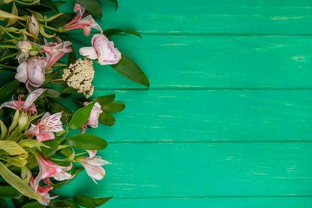 Вид сверху светло-розовых цветов с ветвями листьев на зеленой поверхности Бесплатные Фотографии