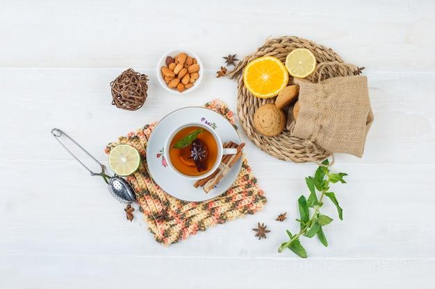 Вид сверху лаймов и печенья на круглой подставке с чашкой чая Бесплатные Фотографии