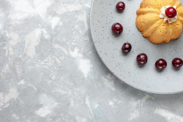 灰色のライト、ケーキビスケットシュガースイートベイクフルーツのプレート内にチェリーと小さなケーキの上面図 無料写真