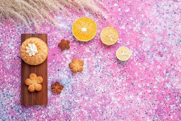 Вид сверху маленького торта с печеньем и дольками апельсина на розовой поверхности Бесплатные Фотографии