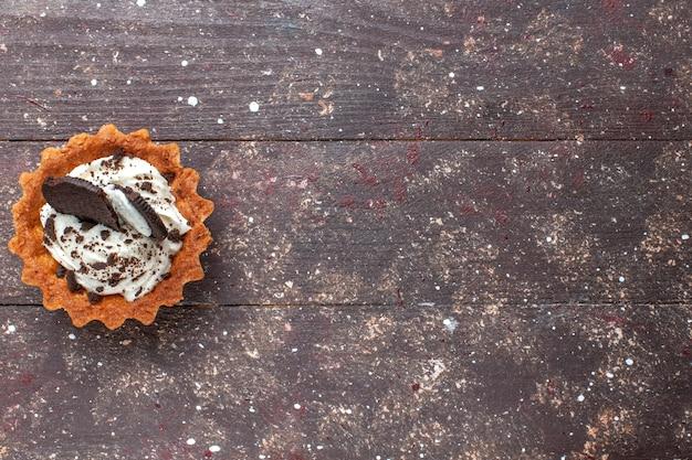 Вид сверху маленького торта со сливками и шоколадом, изолированного на деревянном коричневом, бисквитном пироге Бесплатные Фотографии