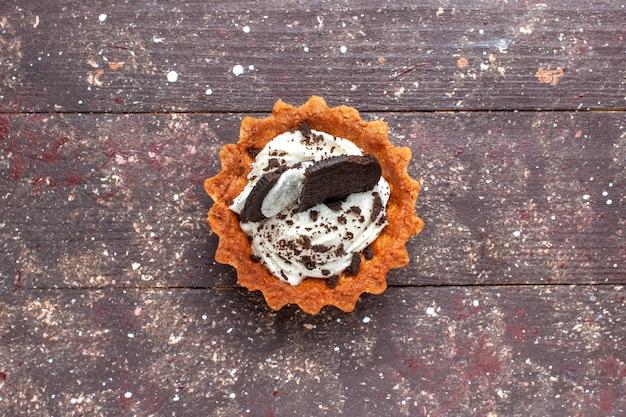 Вид сверху маленького торта со сливками и шоколадом, изолированного на деревянном коричневом, бисквитном сладком пироге Бесплатные Фотографии