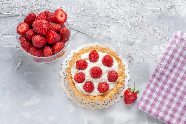 Вид сверху маленького торта со сливками и свежей красной клубникой на свете, торт фруктовый ягодный бисквитный крем Бесплатные Фотографии
