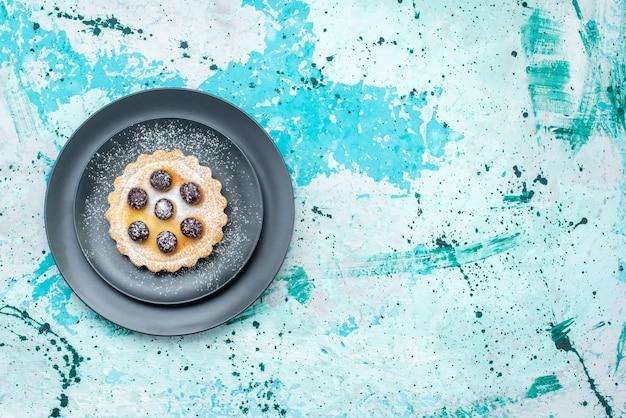 水色のパイフルーツケーキ焼きのプレート内に砂糖粉とサクランボの小さなケーキの上面図 無料写真