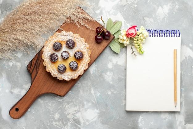砂糖粉フルーツクリームとライト、ケーキクリームフルーツスウィートティーのメモ帳と小さなケーキの上面図 無料写真