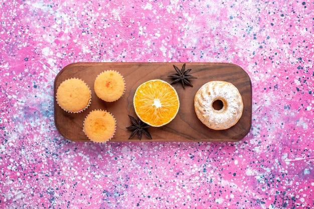 Вид сверху маленьких пирожных с долькой апельсина на розовой поверхности Бесплатные Фотографии