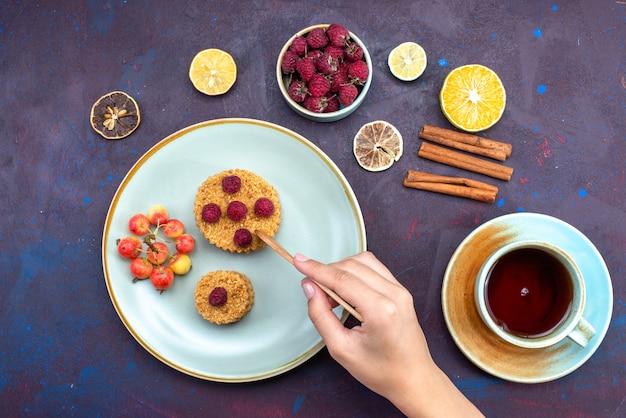 어두운 표면에 과일 계피 차 접시 안에 신선한 나무 딸기와 작은 둥근 케이크의 상위 뷰 무료 사진