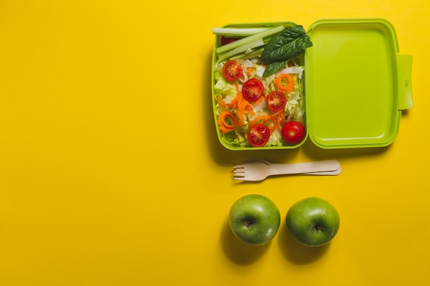 Top view of lunch box with salad and two apples Free Photo