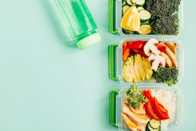 テキストのための空きスペースと緑の背景に食品米肉野菜と果物のランチボックスの上面図 Premium写真
