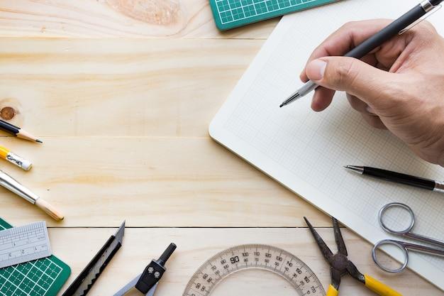 Вид сверху мужской руки на деревянном столе с элементами инструментов, оборудования Premium Фотографии