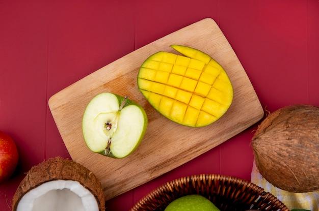 Вид сверху манго с разрезанным пополам зеленым яблоком на деревянной кухонной доске на красной поверхности Бесплатные Фотографии