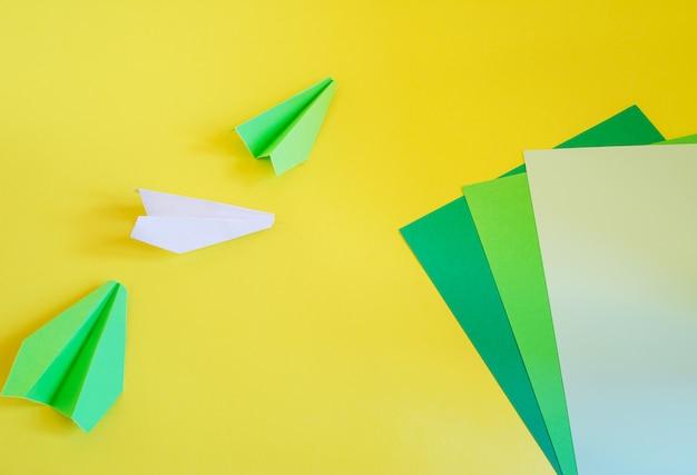 노란색에 누워 많은 세 종이 비행기의 상위 뷰 프리미엄 사진
