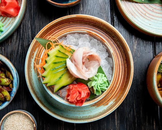 ニシンのマリネフィレのマリネ、スライスしたキュウリジンジャーとわさびソースの木製テーブルの上の皿に氷の上面図 無料写真