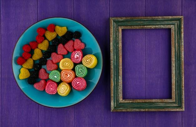コピースペースと紫色の背景にプレートとフレームのマーマレードのトップビュー 無料写真