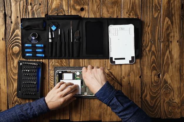Вид сверху мастера ремонтируют сломанный планшет рядом с сумкой для инструментов и на деревянном столе в сервисной лаборатории Бесплатные Фотографии