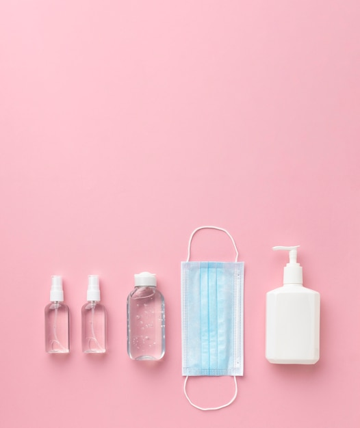 Вид сверху медицинской маски с дезинфицирующим средством для рук и бутылкой с жидким мылом Premium Фотографии