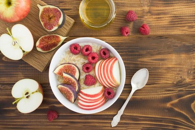 木製のテーブルのボウルにイチジク、ラズベリー、リンゴとミルクオートミールのトップビュー Premium写真