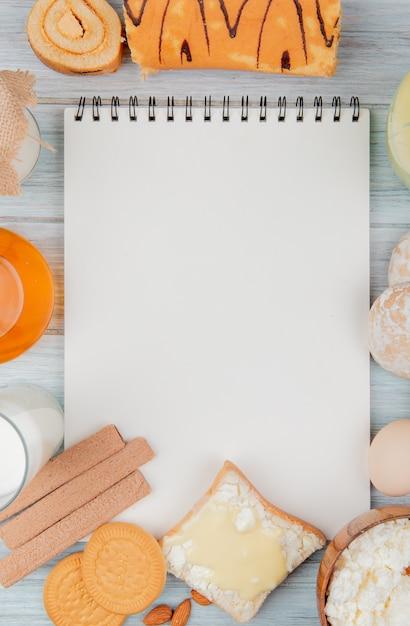 Вид сверху молочных продуктов в качестве творога с молочным кремом и печеньем обваляет яйцо вокруг блокнота на деревянном фоне с копией пространства Бесплатные Фотографии