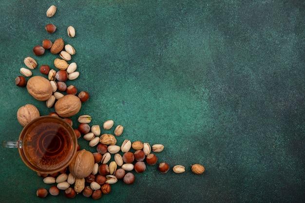 Вид сверху на смесь орехов, грецких орехов, фисташек, фундука и арахиса с чашкой чая на зеленой поверхности Бесплатные Фотографии