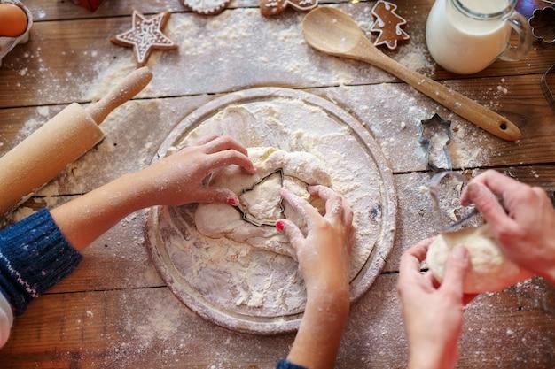 Взгляд сверху рук матери и ребенк делая печенья рождественской елки. Premium Фотографии